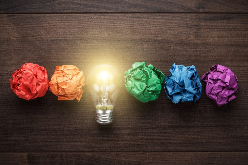 5 balls of colour paper scrunched up in a line with a light bult in the middle
