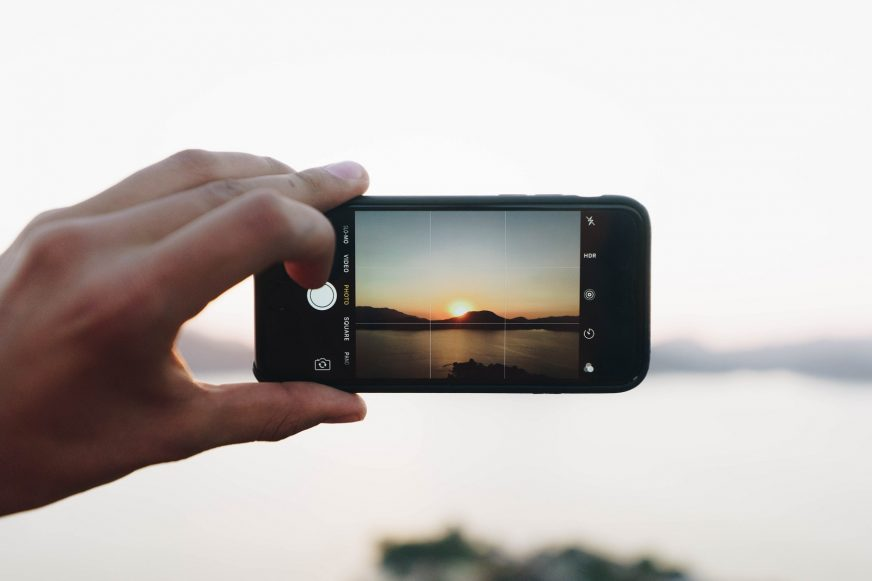 person taking photo of a sunset on a phone