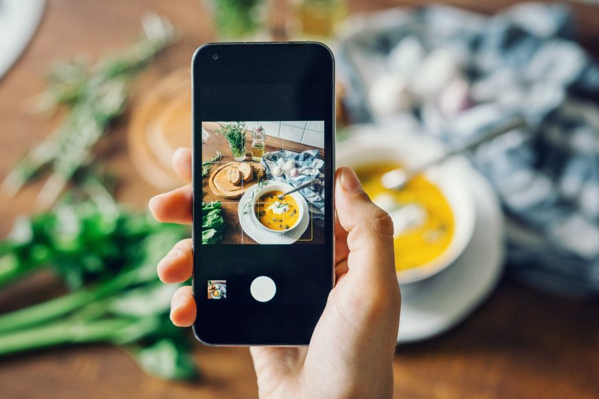 Someone holding a mobile phone to take a picture of a bowl of soup