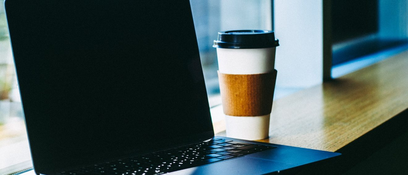 laptop in cafe next to coffee cup