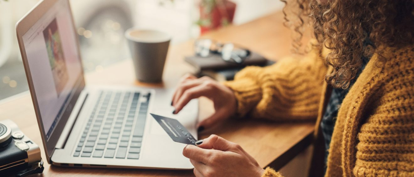 woman uses credit card on laptop