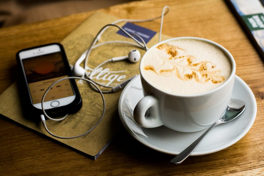 coffee cup with a mobile phone and headphones