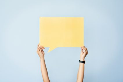 A person holding up a paper speech bubble