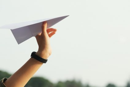 hand holding paper plane